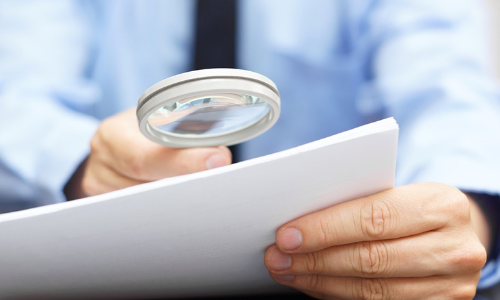 man examining papers with magnifying glass for financial fraud