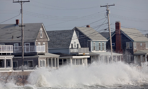 storm waves crashing into seawall in front of houses
