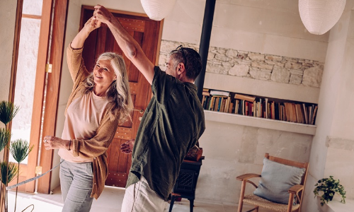 happy mature couple dancing at home in retirement