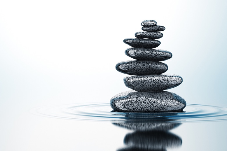 Stack of balancing rocks on still water