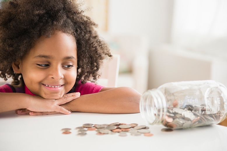 Young girl looking at jar of coins spilled on table