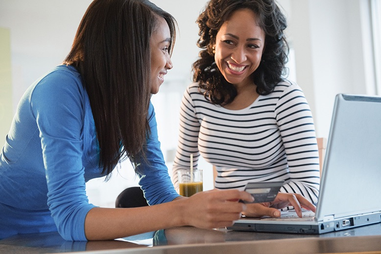 two women smiling while online shopping with credit card