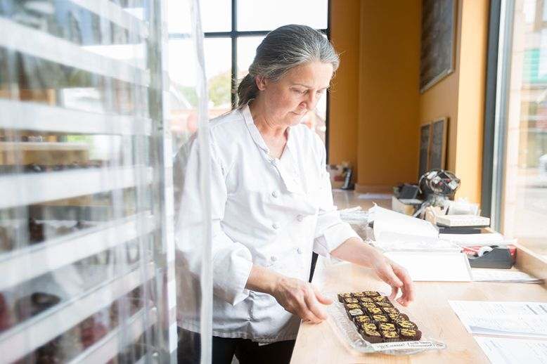 Woman in chef jacket packing chocolates