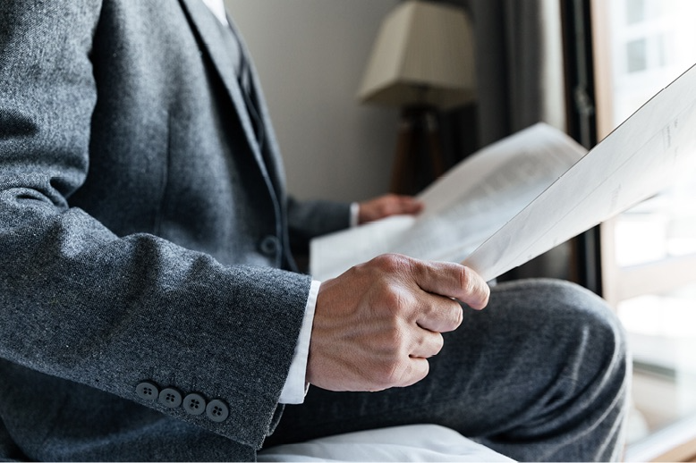 Cropped photo of man in suit reading newspaper in hotel