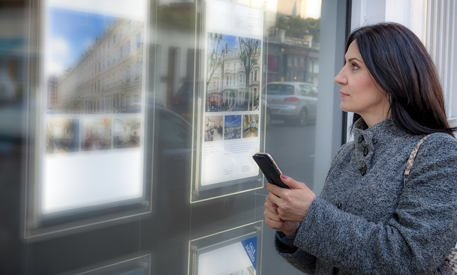 woman looking at a display of images with phone in hand