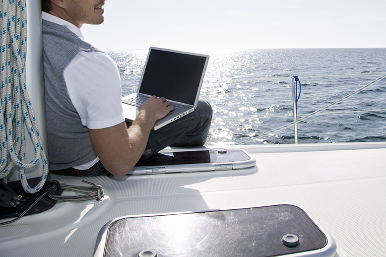 Male using a computer on a boat